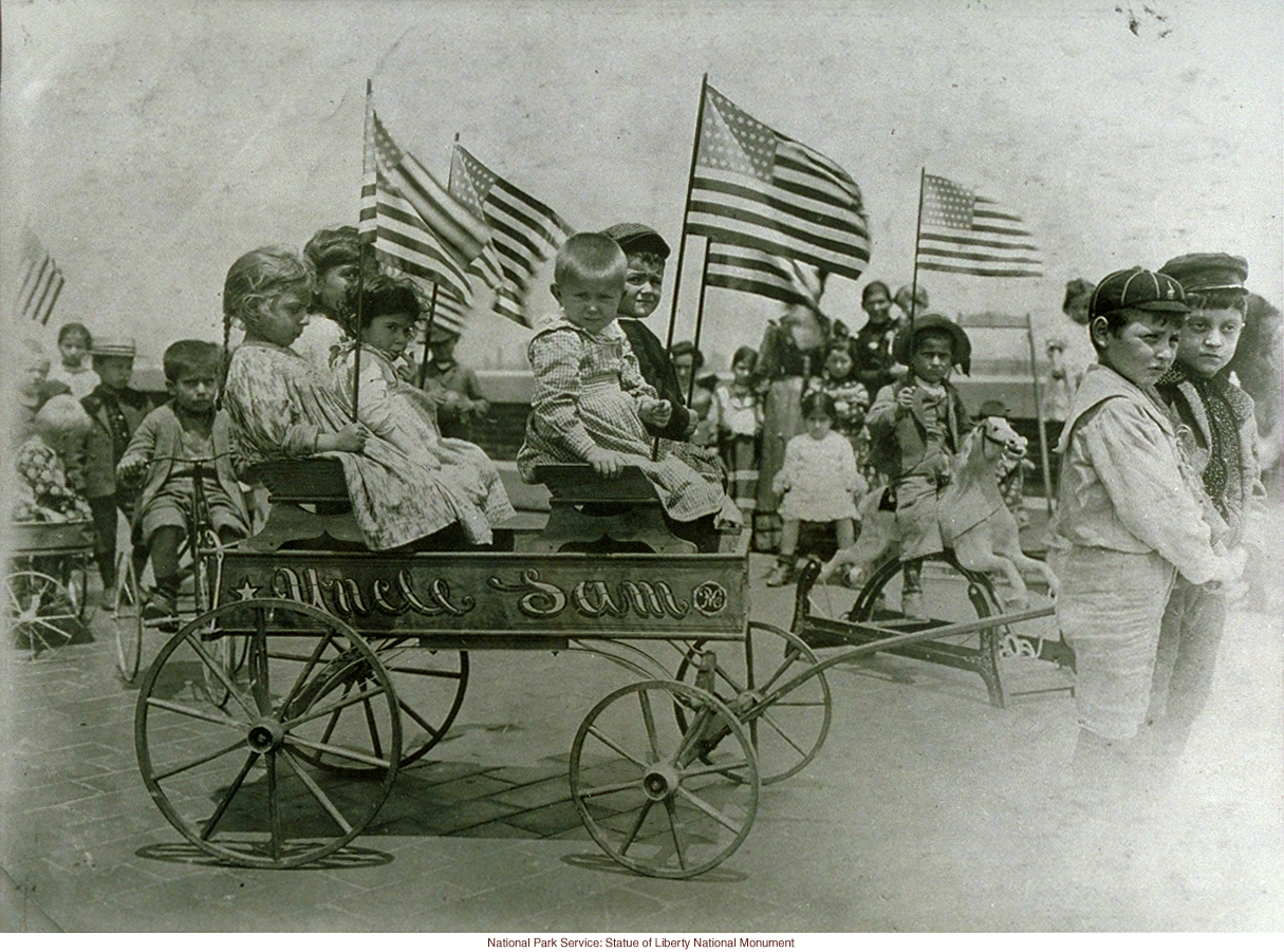 Immigrant children on &quote;roof garden&quote; playground at Ellis Island, with &quote;Uncle Sam&quote; cart (Photograph by Augustus Sherman)