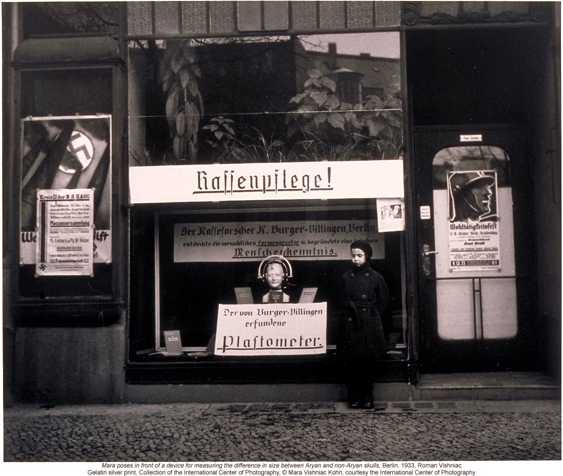 Nazi propaganda in Berlin storefront, including anthropometric device for measuring differences between Aryan & Non-Aryan skulls (by Roman Vishniac)